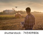 attractive farmer navigating... | Shutterstock . vector #745409806