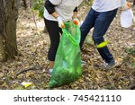 picking up trash in the forest. ... | Shutterstock . vector #745421110