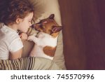 Stock photo sweet curly girl and jack russell dog is sleeping in night 745570996