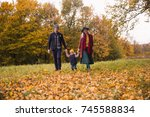 the young happy family walking... | Shutterstock . vector #745588834