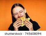 the girl eagerly eats a large... | Shutterstock . vector #745608094