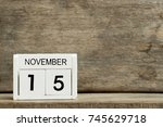 Small photo of White block calendar present date 15 and month November on wood background