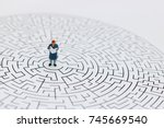 Small photo of Miniature people: Businessman reading on center of maze. Concepts of finding a solution, problem solving and challenge.