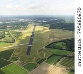 Small photo of 31 July 2017, Enschede, Holland. Aerial view of Twente Airport, a former military Dutch airforce base. The black runway is surrounded by green grass. A cloud shade is over the field. A clear horizon.