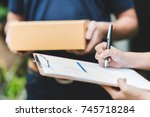 Small photo of Close up shot of woman hand putting signature in clipboard to receive package from delivery man in background
