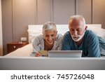 a senior couple is browsing the ... | Shutterstock . vector #745726048