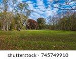 an open green field surrounded... | Shutterstock . vector #745749910