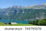 Small photo of The mountain chain Churfirsten in Switzerland and a part of the Lake Walensee, steep rocks and turquoise-colored water/The mountain chain Churfirsten