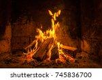 a fire burns in a fireplace ... | Shutterstock . vector #745836700