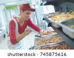 Stock photo buffet female worker servicing food in cafeteria 745875616