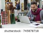 man buying gifts on line while... | Shutterstock . vector #745878718