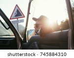 Small photo of Portrait of young middle aged man nomad adventurer leaning towards window shelf of his car or camping van. concept travel, freedom, sunset, exciting adventures road trip