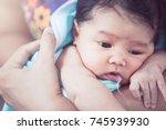 mother burping her newborn baby ... | Shutterstock . vector #745939930