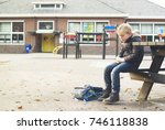 sad boy outside at schoolyard | Shutterstock . vector #746118838