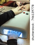 Small photo of Creating a basic manicure in the beauty salon master on the model. Applying gel varnish to the fingernails, and drying the varnish in an ultraviolet lamp