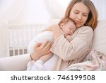 young mother holding sleeping... | Shutterstock . vector #746199508