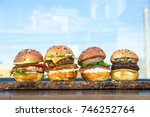 four burgers on wooden board in ... | Shutterstock . vector #746252764