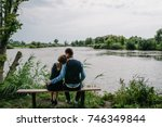 a young couple sitting back on... | Shutterstock . vector #746349844