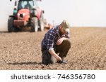 young farmer is examing dirt... | Shutterstock . vector #746356780