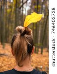 Small photo of A girl with a beautiful hairstyle and a yellow leaf on her head looks in front of her in the autumn forest (purpose, plan, determination, readiness, purposefulness, forward - the concept)