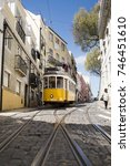 Small photo of A yellow old tram riding down San Vicente street, next to the monastery of São Vicente de Fora, Lisbon city, Portugal