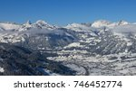 Small photo of Village Saanen and snow covered mountains. Winter scene in the Bernese Oberland, Switzerland.