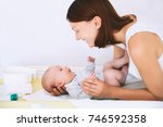 mom gently care of baby on... | Shutterstock . vector #746592358