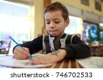 kid drawing at table in a... | Shutterstock . vector #746702533