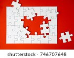 Small photo of half complete white color puzzle on red background. Task for completion concept. selective focus