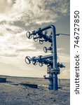 Small photo of Wellhead with valve armature. Oil and gas industry concept. Industrial site background. Toned.