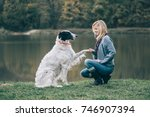 girl and her dog playing... | Shutterstock . vector #746907394