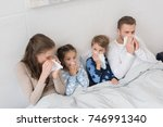 sick family lying in a bed and... | Shutterstock . vector #746991340