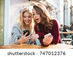 two excited young girls using... | Shutterstock . vector #747012376