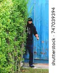 Small photo of Mask thief in balaclava with holding knife ,Outlaw bad man hold weapon pointing to victim