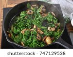 Small photo of Sauteing spinach and mushrooms in a cast iron skillet