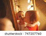 little girl kisses herself in... | Shutterstock . vector #747207760
