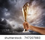 man's hand is holding gold cup... | Shutterstock . vector #747207883