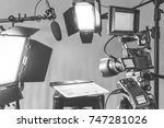 Small photo of Professional video camera, lights and microphone equipment all set up for an interview in a studio setting.