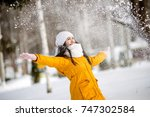 Young Woman Throwing Snow ...