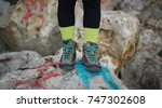 Small photo of Close up of woman feet wearing yellow wool socks and staying on rocks with graffiti. Autumn time always be and stay positive concept