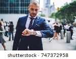 pensive businessman checking... | Shutterstock . vector #747372958