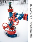 Small photo of Production wellhead with valve armature. Oil, gas industry. Petroleum theme.
