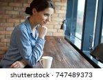beautiful brunette using laptop ... | Shutterstock . vector #747489373