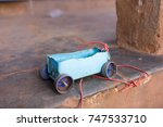 Small photo of A simple toy car made of a plastic box, bottle caps and skewer sticks