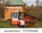 Small photo of Work on the construction site of an ecological house. The excavator adjusts the terrain. A small digger in the garden