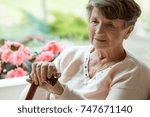 elder woman sitting on white... | Shutterstock . vector #747671140