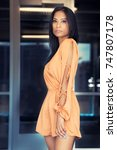 Small photo of Beautiful exotyic young woman wearing romper dress