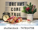 Small photo of Christmas composition with festive accoutrement and board with phrase, sentence dreams come true.