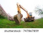 a yellow tractor mows the grass ... | Shutterstock . vector #747867859