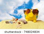 piggy bank on beach vacation   Shutterstock . vector #748024834